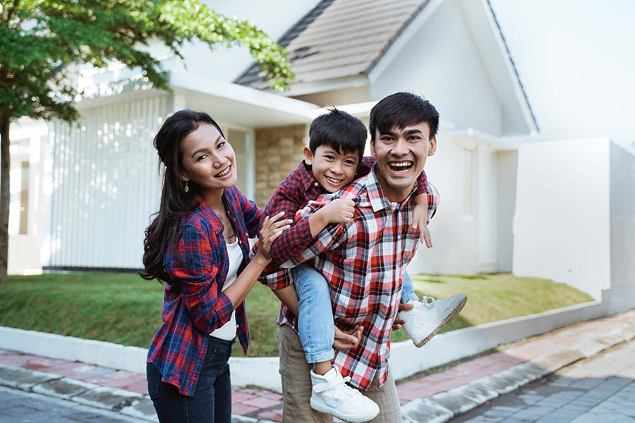 Personal Insurance - Happy Young Family Standing Outside Their Home On Sunny Day